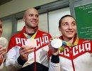 Бронзовый призер ОИ-2016 в Рио Денис Дмитриев (в центре) и серебряные призеры Игр Анастасия Войнова (слева) и Дарья Шмелева, в аэропорту Шереметьево
