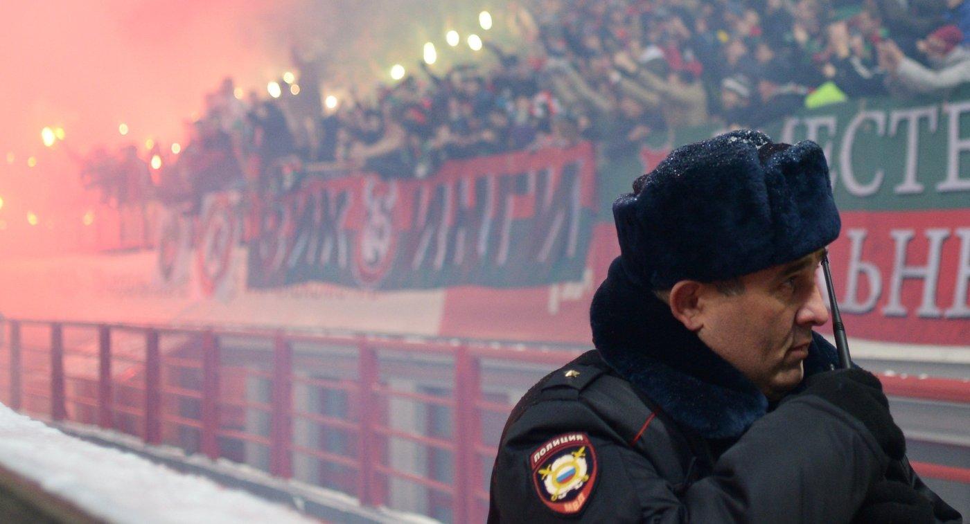 Болельщики и сотрудник полиции на матче РФПЛ