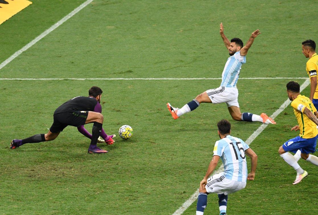 Нападающий сборной Аргентины Серхио Агуэро (в центре) и вратарь сборной Бразилии Алиссон (слева)