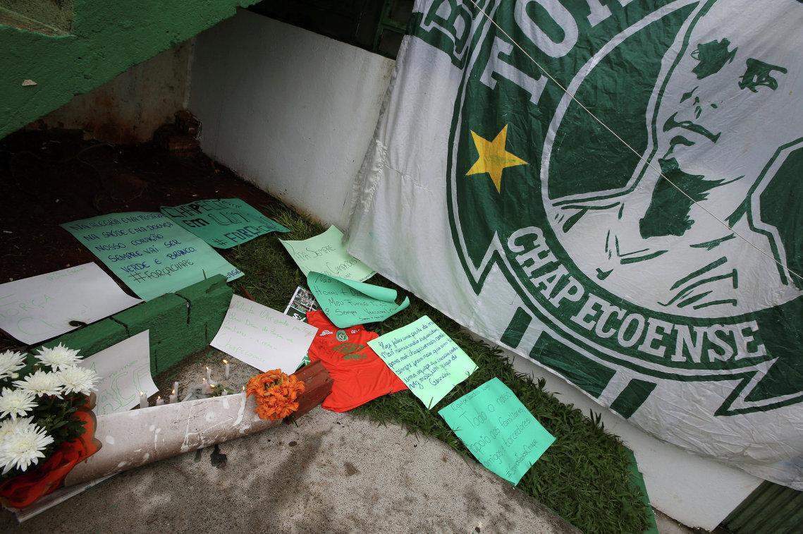 Цветы и записки рядом с флагом футбольного клуба Шапекоэнсе