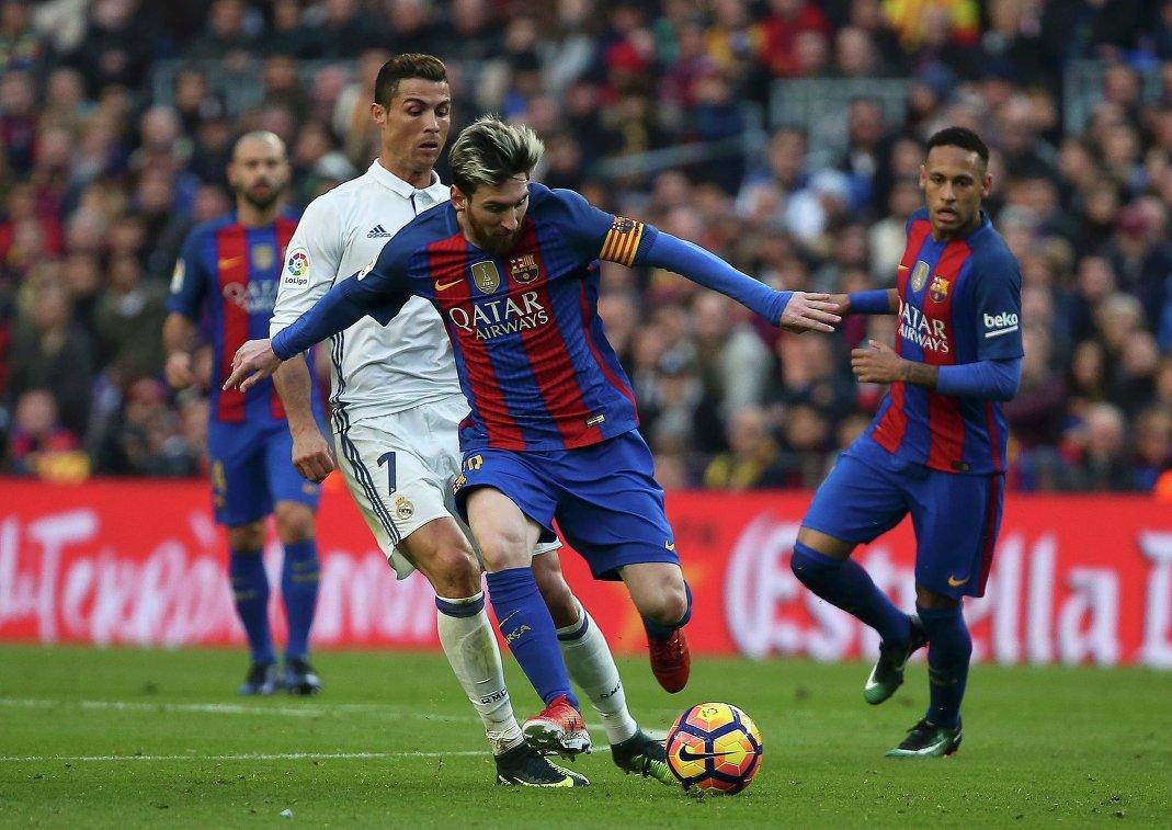 Нападающий мадридского Реала Криштиану Роналду и форвард Барселоны Лионель Месси (слева направо) в борьбе за мяч
