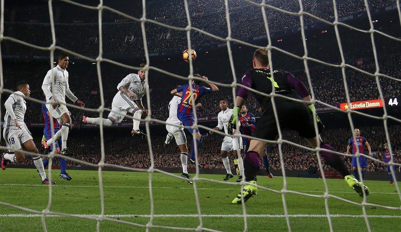 Защитник мадридского Реала Серхио Рамос (в центре) забивает мяч в ворота голкипера Барселоны Марка-Андре Тер Штегена
