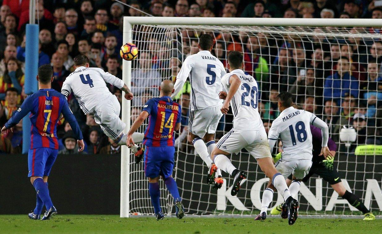 Защитник мадридского Реала Серхио Рамос (второй слева) забивает мяч в ворота голкипера Барселоны Марка-Андре Тер Штегена