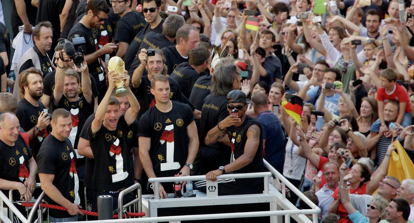 Футболисты сборной Германии показывают кубок поклонникам футбола