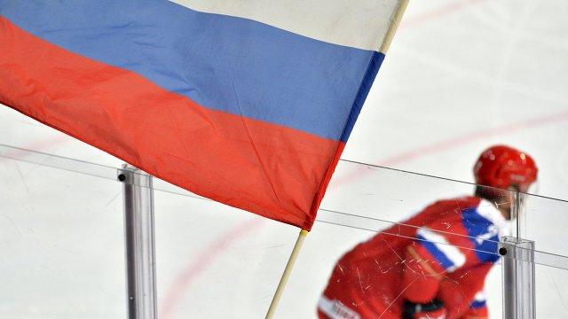 Болельщик сборной России держит флаг во время хоккейного матча
