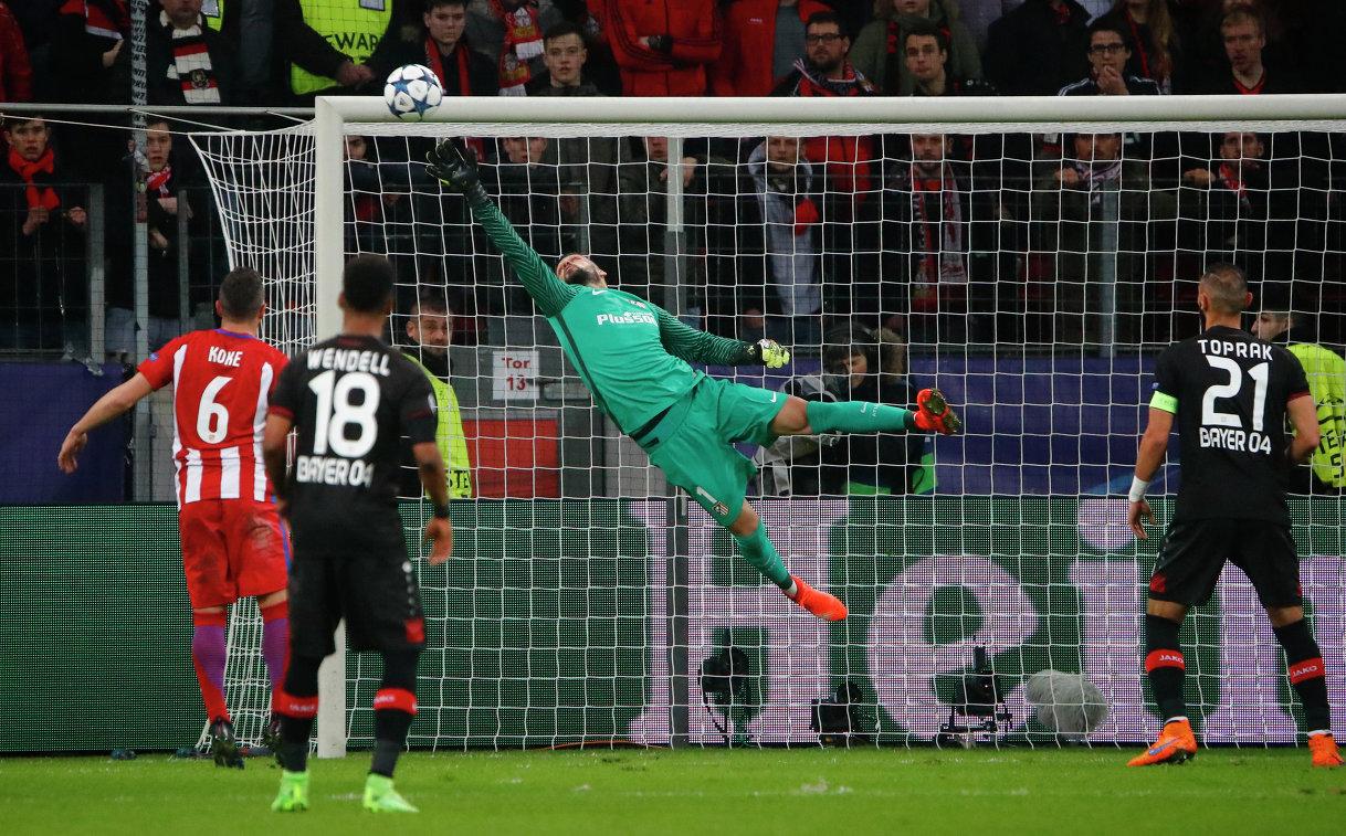 Голкипер Атлетико Анхель Мойя (в центре) отбивает мяч после удара футболиста Байера