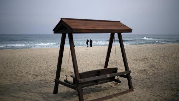 Мужчины в деловых костюмах на пляже Gyeongpo Beach в городе Каннын, Республика Корея