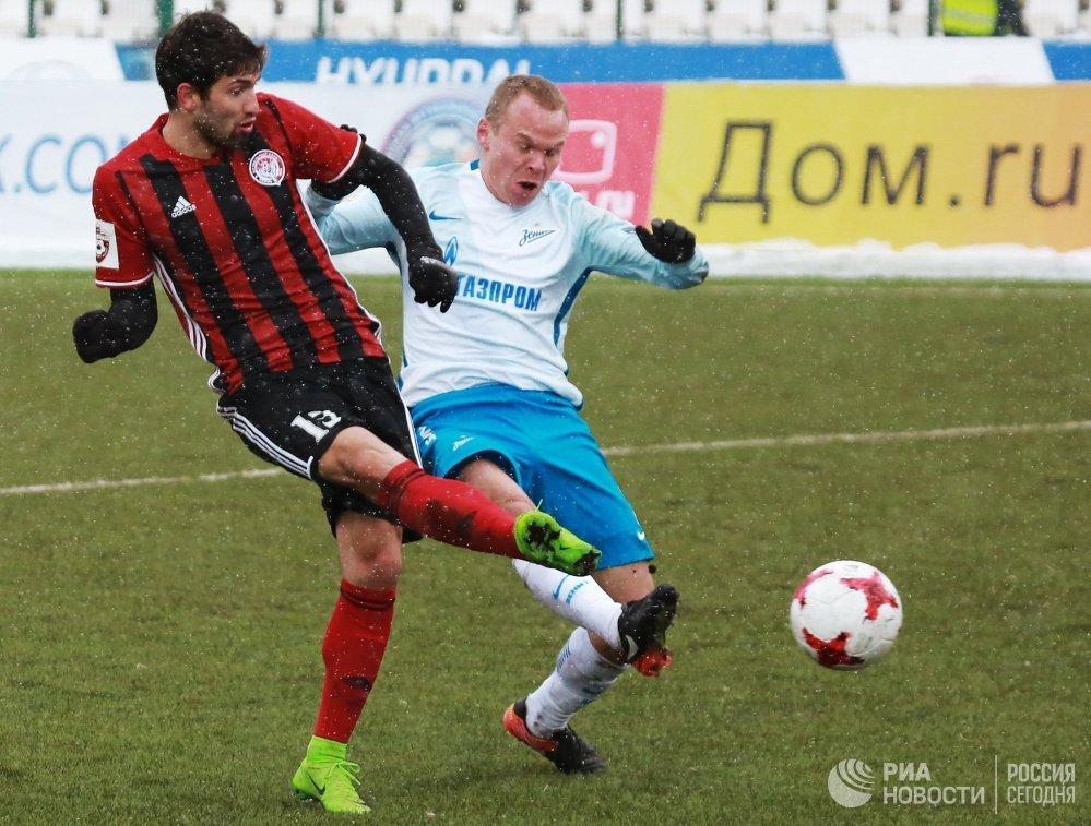 Защитники ФК Амкар Роланд Гиголаев (слева) и ФК Зенит Александр Анюков