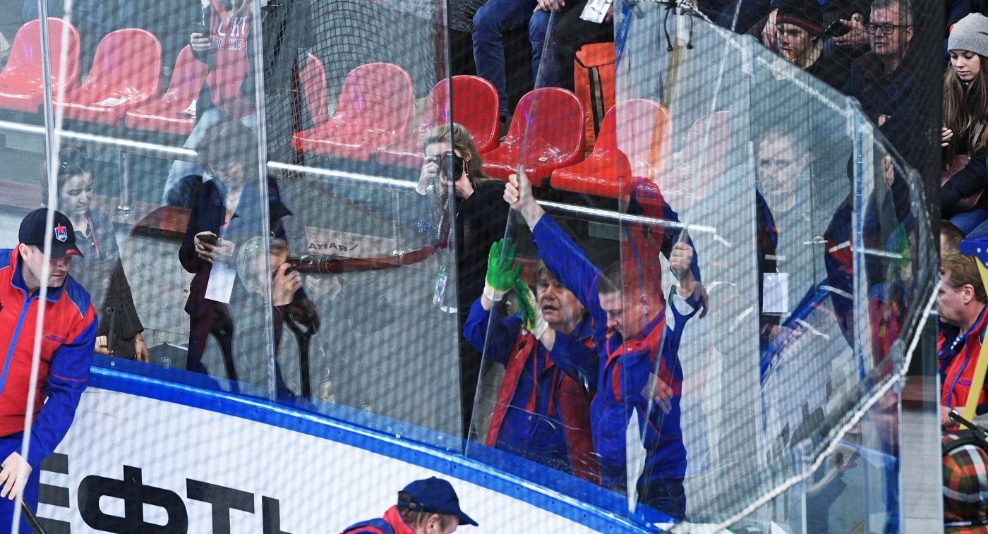 Сотрудники спортивной арены устанавливают новое стекло ограждения игровой площадки на матче 1/4 финала плей-офф Кубка Гагарина КХЛ ЦСКА - Локомотив