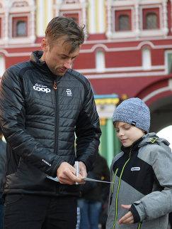Норвежский лыжник Петтер Нортуг дает автограф юному поклоннику во время прогулки на Красной площади