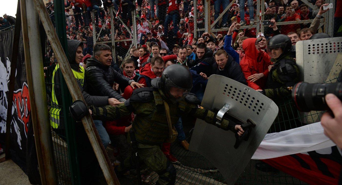 Сотрудники правоохранительных органов сдерживают болельщиков московского Спартака, прорывающихся на поле