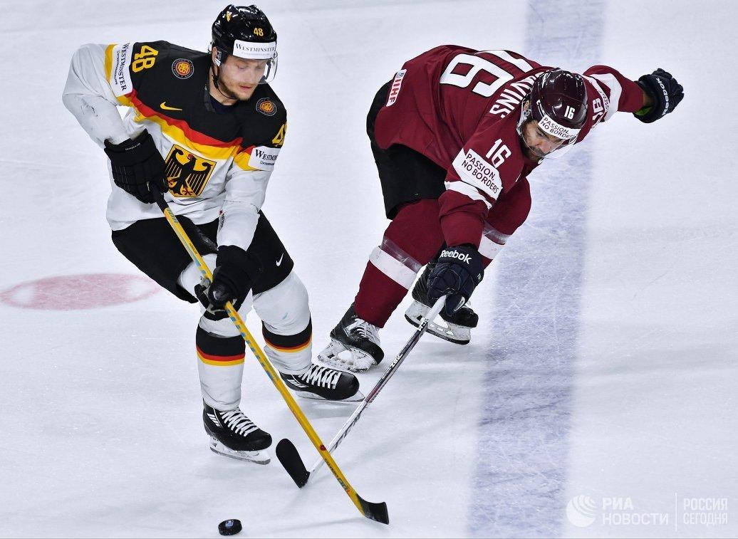 Защитник сборной Германии Франк Хёрдлер и нападающий сборной Латвии Каспарс Даугавиньш (справа)