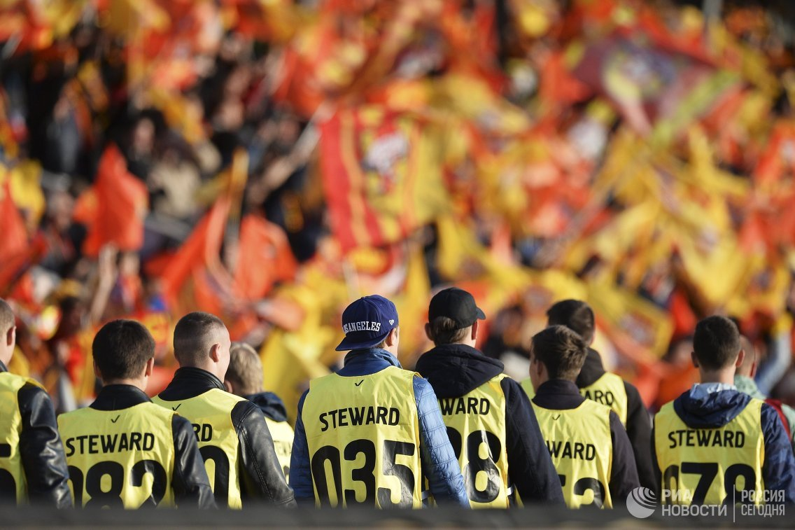 Стюарды на фоне трибуны с болельщиками фк Арсенал