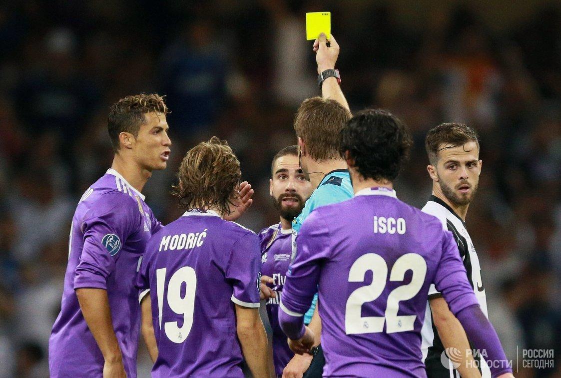 Главный судья матча Феликс Брих показывает жёлтую карточку защитнику Реала Даниэлю Карвахалю (третий слева)