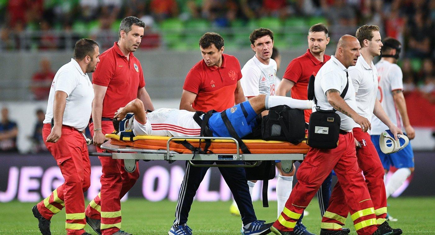 Медики уносят с поля получившего травму полузащитника сборной России Романа Зобнина