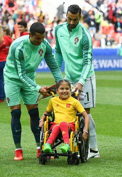 Нападающий сборной Португалии по футболу Криштиану Роналду, вратарь Руй Патрисиу и Полина Хаерединова (слева направо)