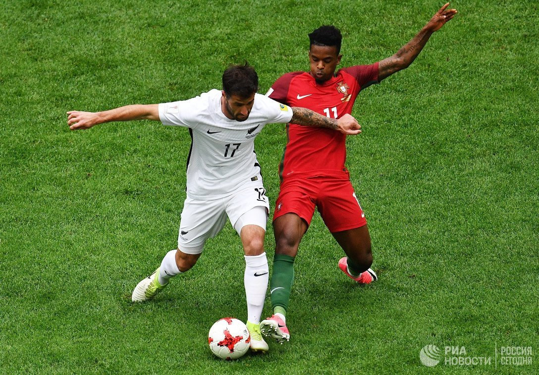Защитник сборной Новой Зеландии Томас Дойл (слева) и защитник сборной Португалии Нелсон Семеду
