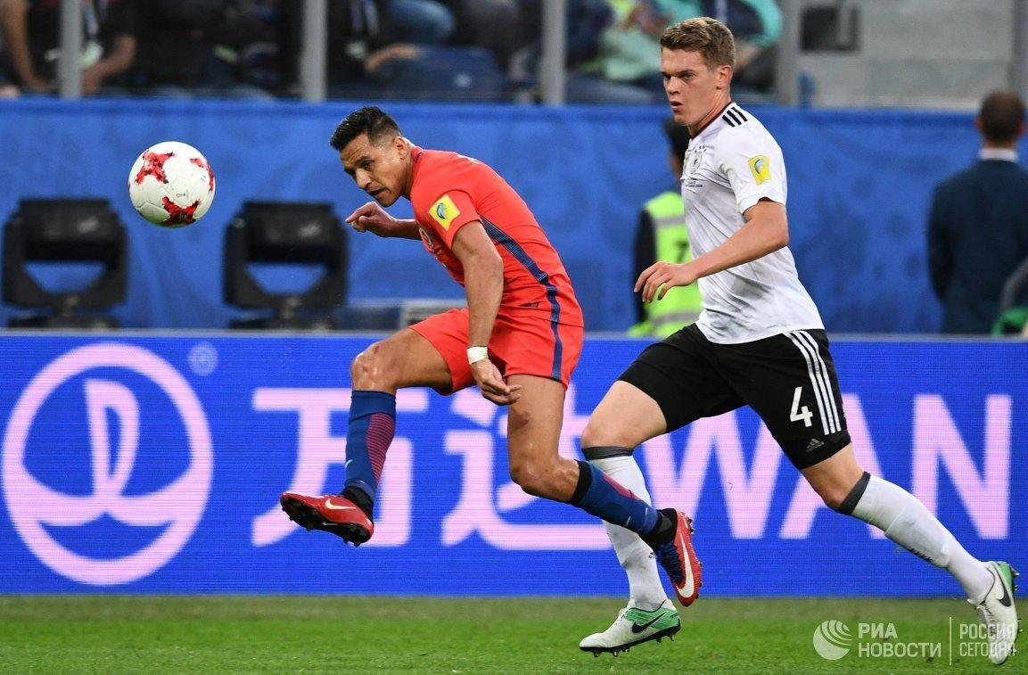 Нападающий сборной Чили по футболу Алексис Санчес и защитник команды Германии Маттиас Гинтер (слева направо)