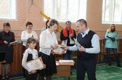 Анатолий Шмелёв вручает золотые знаки ГТО ученице 1-го класса и ее классной руководительнице. Кострома