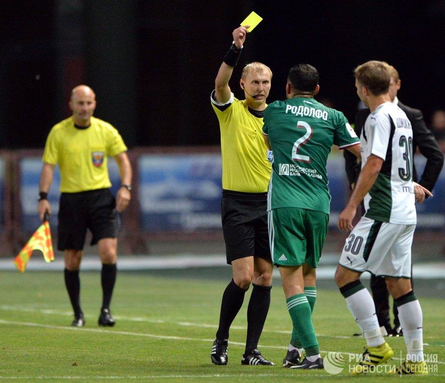 Главный судья Сергей Иванов показывает желтую карточку защитнику Ахмата Родолфо (слева направо)