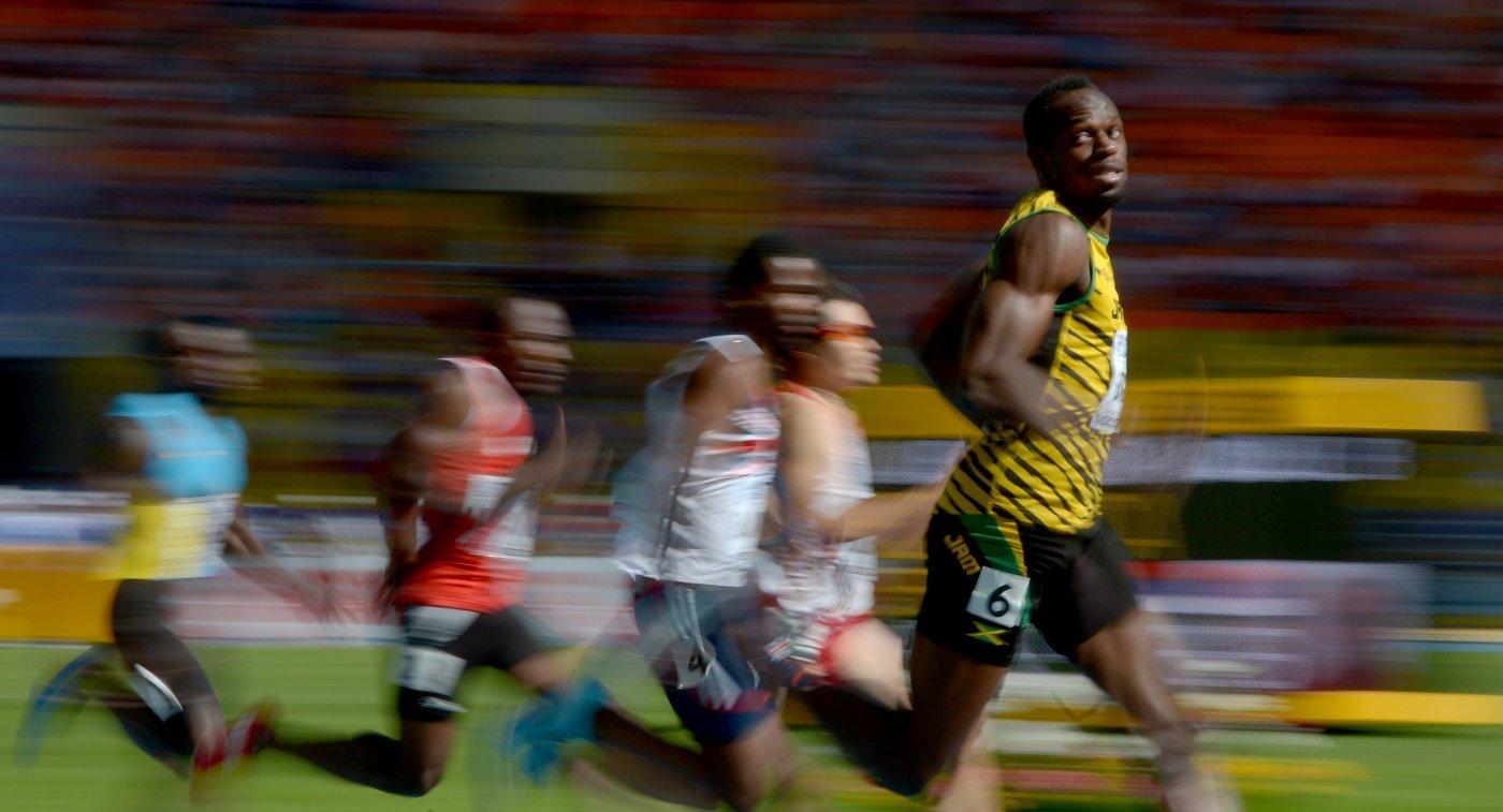 Ямайский спортсмен Усэйн Болт (справа) в предварительном забеге на 200 м