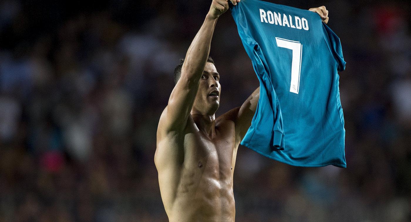 Форвард Реала Криштиану Роналду держит свою футболку после забитого мяча