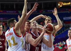 Баскетболисты сборной России Никита Курбанов, Андрей Воронцевич и Тимофей Мозгов (слева направо на заднем плане) и форвард сборной Латвии Роландс Шмитс (на первом плане)