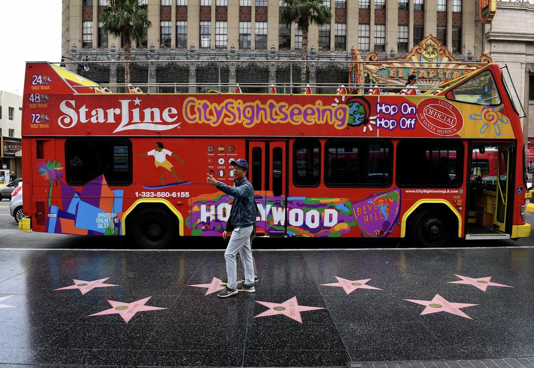 Турист во время прогулки по бульвару в Голливуде