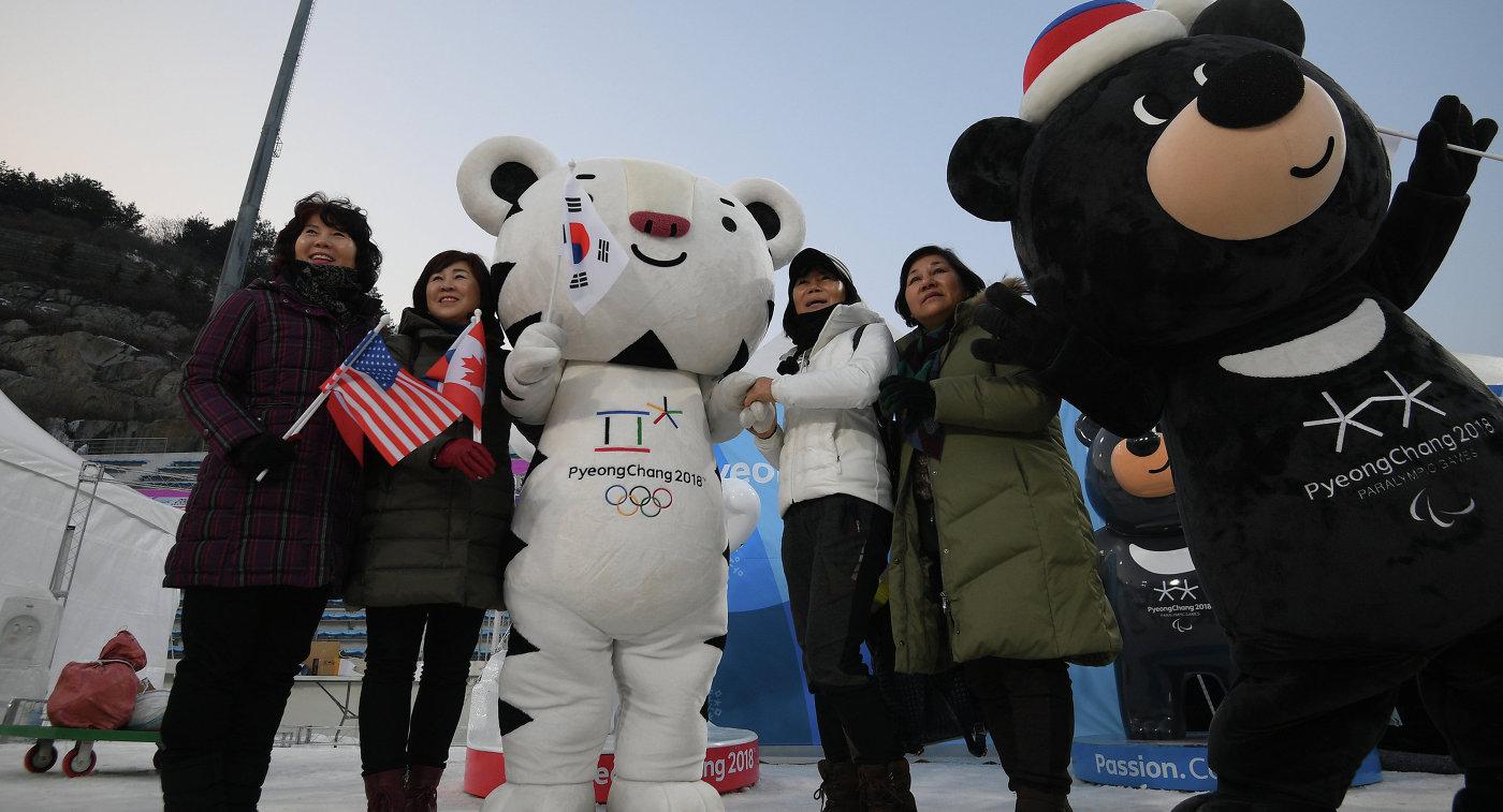 Зрители фотографируются с талисманами зимних Олимпийских игр 2018 года в Пхенчхане