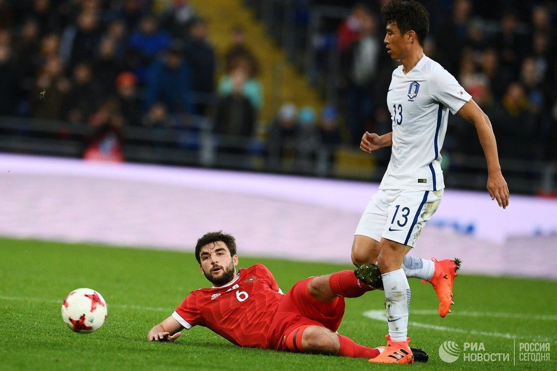 Защитник сборной России Георгий Джикия (Россия) и хавбек сборной Южной Кореи Ку Джа Чхоль (слева направо)