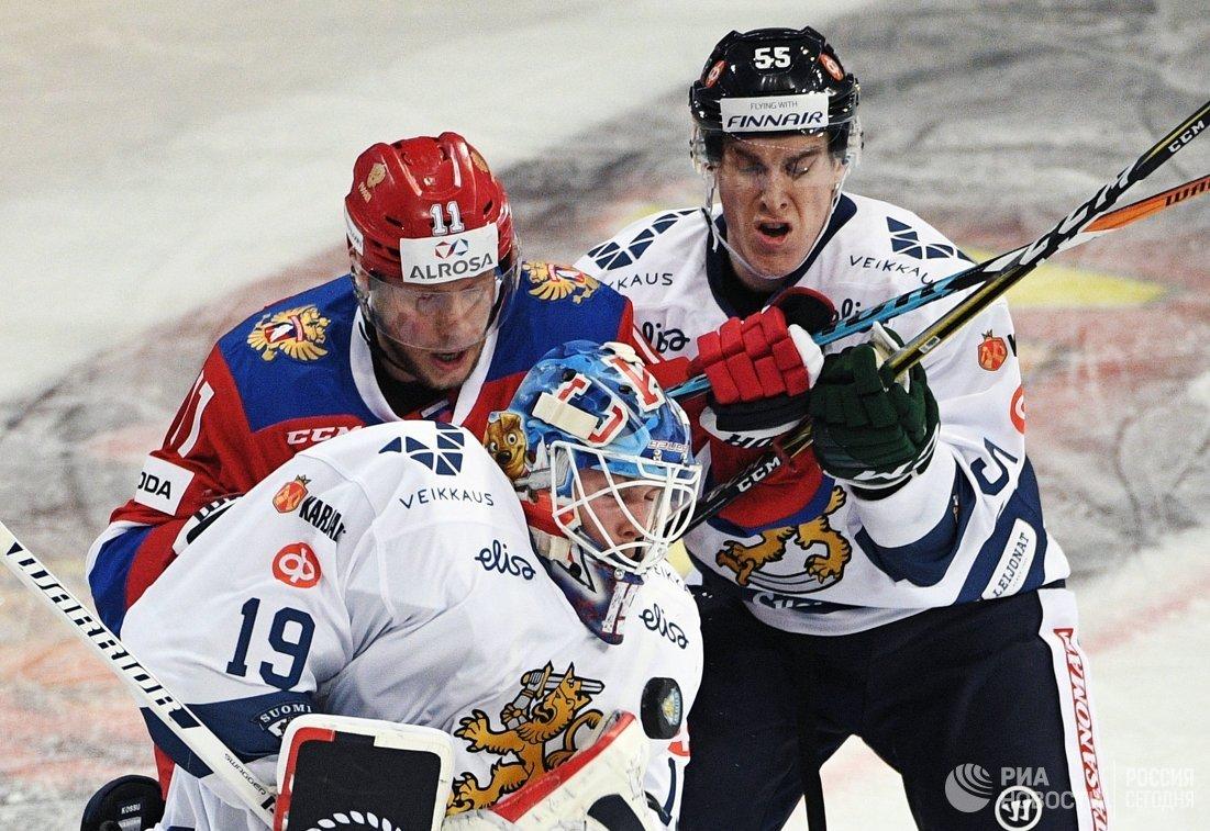 Вратарь сборной Финляндии Микко Коскинен (на первом плане) и форвард сборной России Сергей Андронов (слева на втором плане)