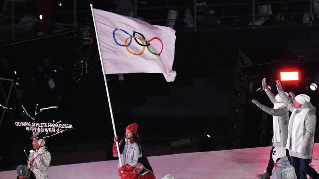 Волонтер несет олимпийский флаг и олимпийские атлеты из России