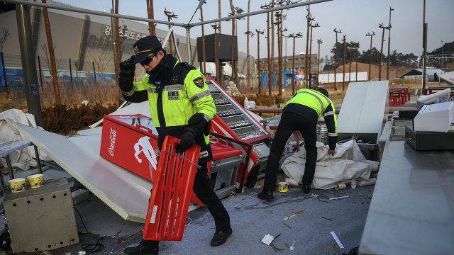 Полицейские во время эвакуации и демонтажа палаток в Олимпийском парке в Канныне из-за сильного ветра