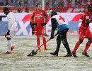 Расчистка от снега красной разметки на футбольном поле во время матча Локомотив - Спартак