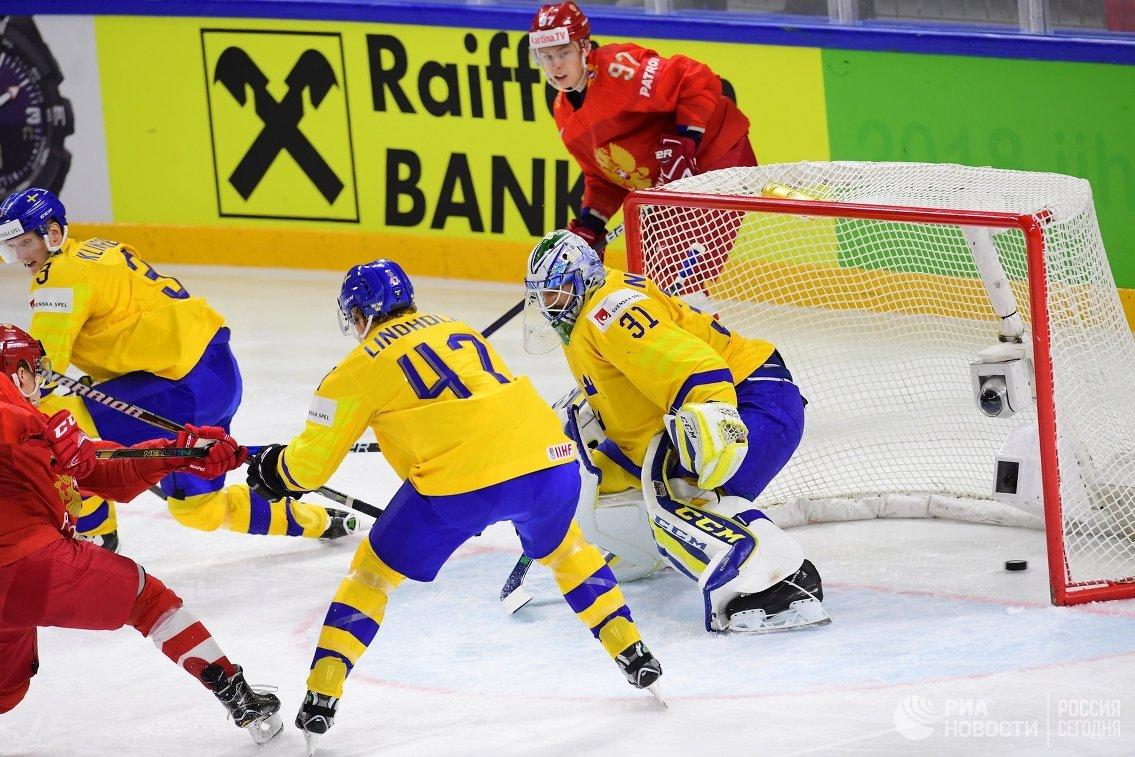 Нападающий сборной России по хоккею Никита Гусев (№97) и вратарь шведов Андерс Нильссон (справа)
