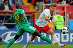 Сенегальский защитник Юссуф Сабали и полузащитник сборной Польши Якуб Блащиковски (Слева направо)