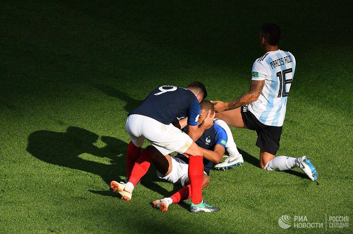 Футболисты сборной Франции Ольвье Жиру, Килиан Мбаппе и аргентинский защитник Маркос Рохо (Слева направо)