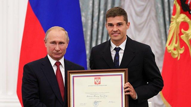 Президент РФ Владимир Путин (слева) и футболист сборной России Роман Зобнин (справа)