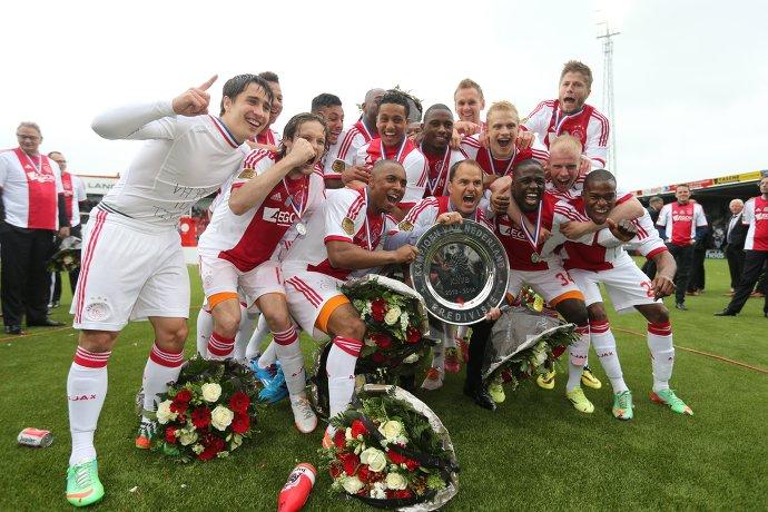 Футболисты Аякса вместе с главным тренером Франком де Буром (в центре снизу) радуются победе в чемпионате Нидерландов по футболу