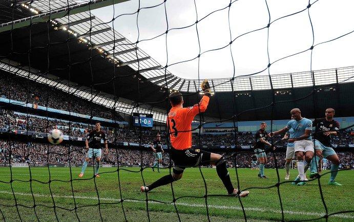 Защитник Манчестер Сити Венсан Компани (второй справа) забивает мяч в ворота Вест Хэма