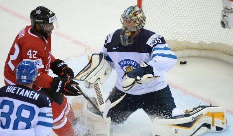Защитник сборной Финляндии Юусо Хиетанен, форвард сборной Канады Джоэль Уорд и вратарь сборной Финляндии Пекка Ринне (слева направо)