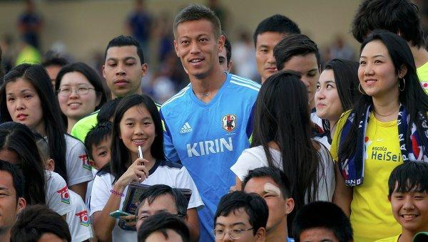 Полузащитник сборной Японии Кэйсукэ Хонда фотографируется вместе с фанатами