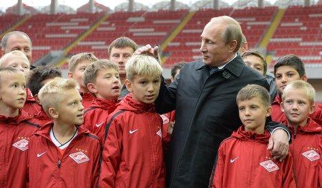 Президент России Владимир Путин с юными футбалистами во время посещения стадиона Открытие Арена - домашнего стадион футбольного клуба Спартак (Москва) в Тушино