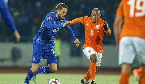 Нападающий сборной Исландии Гильфи Сигурдссон и полузащитник сборной Нидерландов Найджел Де Йонг