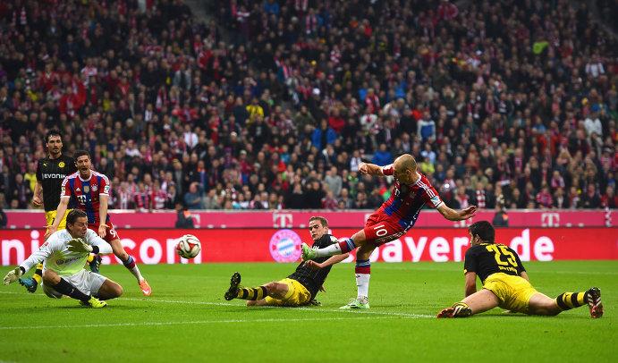 Полузащитник Баварии Арьен Роббен наносит удар по воротам голкипера Боруссии Романа Вайденфеллера (в сером свитере)