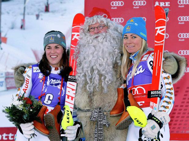 Шведские горнолыжницы Мария Пиетиля-Хольмнер и Фриде Хансдоттер с Санта-Клаусом на подиуме этапе Кубка мира в Оре