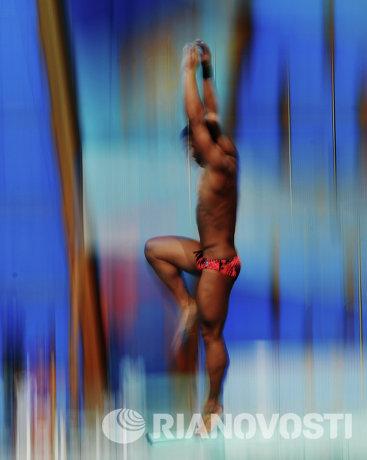 Участник во время разминки перед соревнованиями по прыжкам в воду с трамплина 1 м среди мужчин