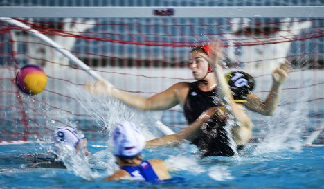 Вратарь сборной Германии по водному поло Бьянка Аренс (на дальнем плане) пропускает мяч в свои ворота