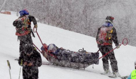 Работники горнолыжной трассы оказывают помощь Линдси Вонн (в центре)