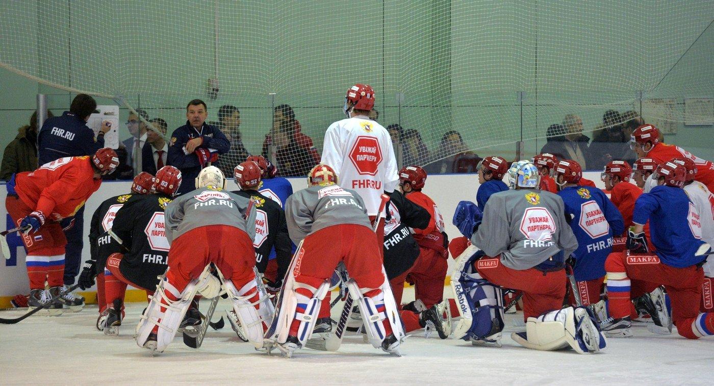 Игроки сборной России по хоккею во время тренировки вместе с главным тренером команды Олегом Знарком (слева на дальнем плане)